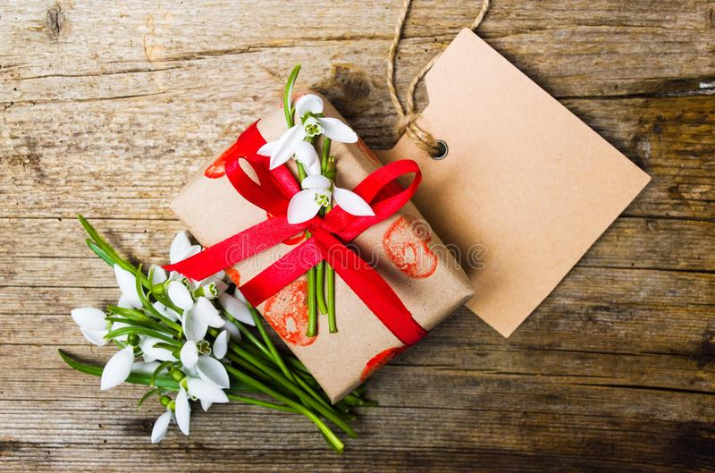 Närvarande ask med snödroppeblommor och ett tomt kort royaltyfri foto