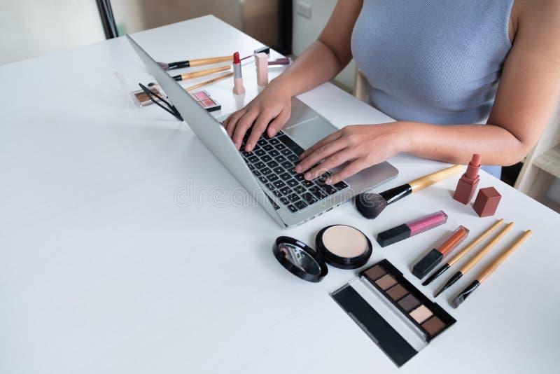 Närvarande kosmetisk produkt för kvinnablogger som direktanslutet sitter den främsta minnestavlan och TV-sändning till det social royaltyfria bilder