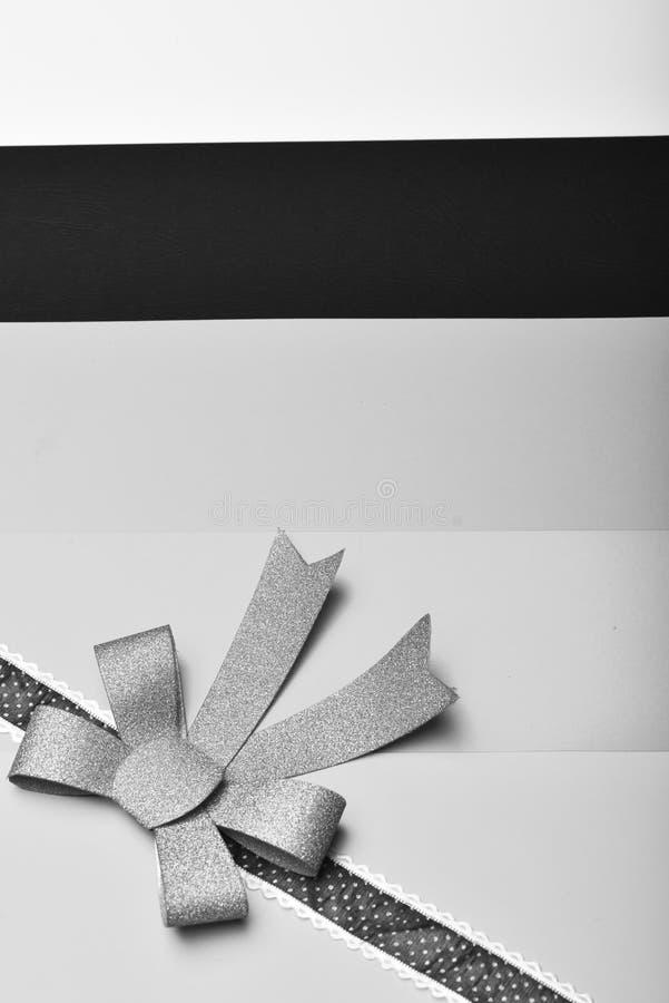 Närvarande sjal med pilbågen i hörn Blå pilbåge på prickigt mörkt band på färgglad randig bakgrund royaltyfri fotografi