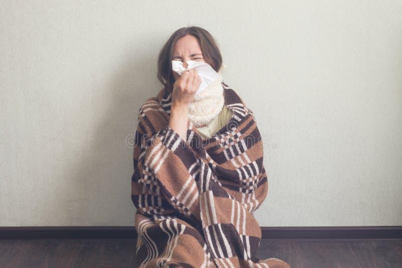 Näsa för ` s för flickaslag ett med det pappers- silkespappret Kvinnan i varm woolen pläd sitter på golv arkivfoton