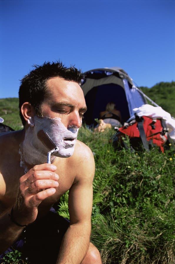 nästa det fria för man som rakar tenten till royaltyfria bilder