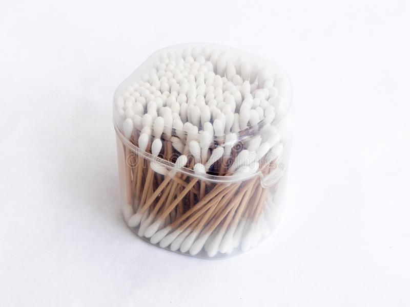 Nästan fullt plast- genomskinligt emballage med bomullsbomullstoppar för att göra ren öronen som isoleras på en vit bakgrund royaltyfri bild