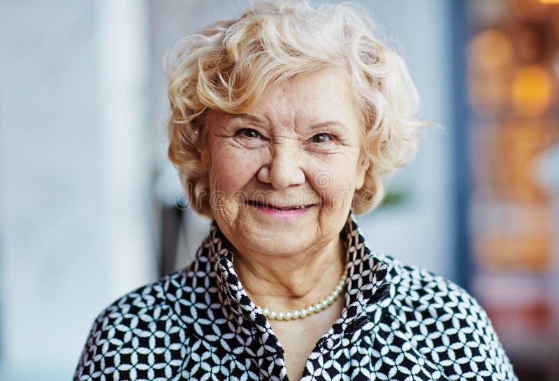 Nätt äldre kvinna mot suddig bakgrund arkivbilder