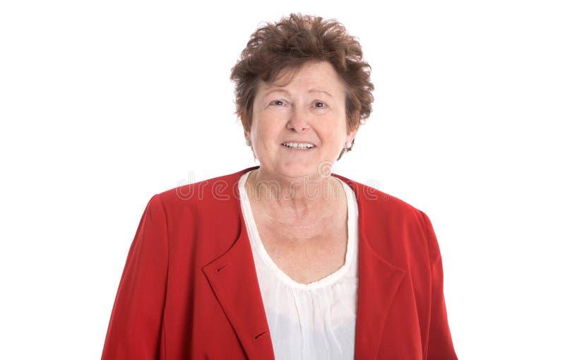 Nätt äldre och le kvinna i rött som isoleras över vit backgr fotografering för bildbyråer