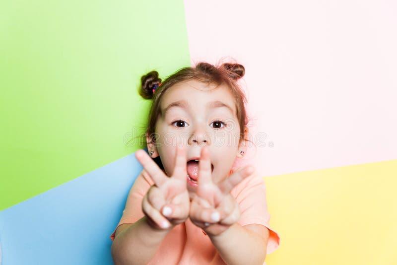 Nätt 4 år liten flicka med den roliga framsidan på flerfärgad bakgrund Ljusa färger och stilfull bild royaltyfri foto