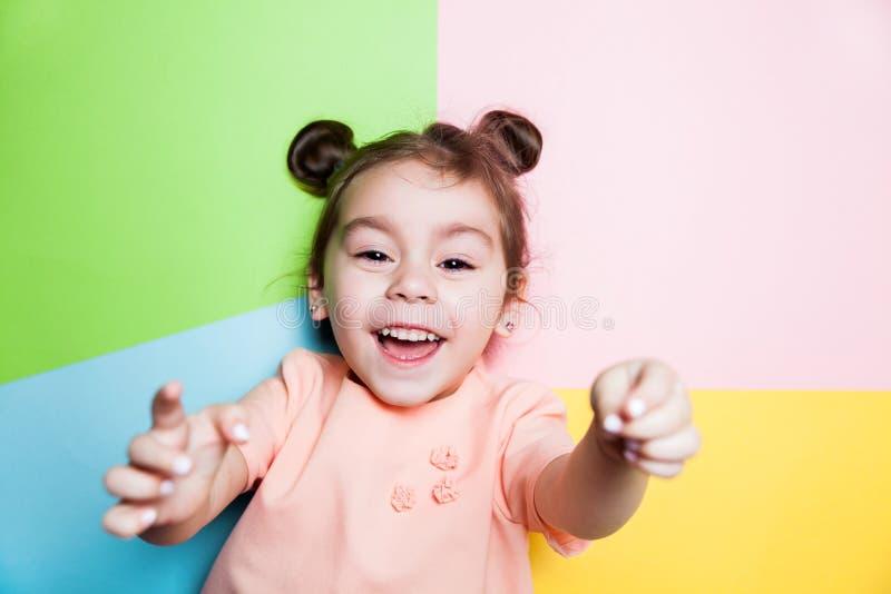 Nätt 4 år liten flicka med den roliga framsidan på flerfärgad bakgrund Ljusa färger och stilfull bild arkivfoton
