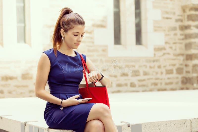 Nätt affärskvinna som ser hennes klocka arkivfoton