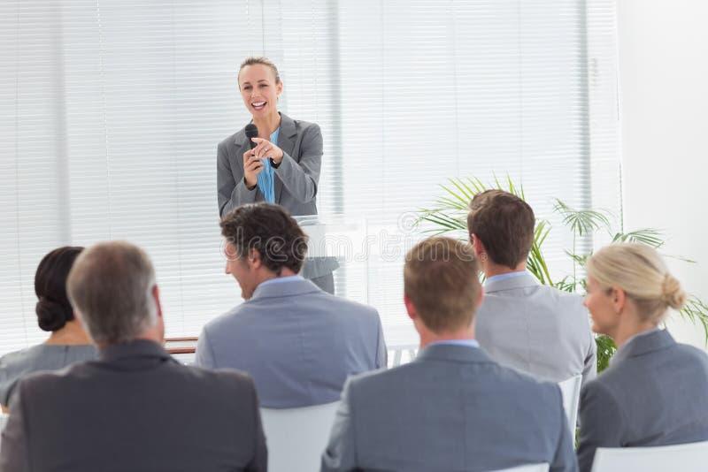 Nätt affärskvinna som talar i mikrofon under konferens royaltyfria foton