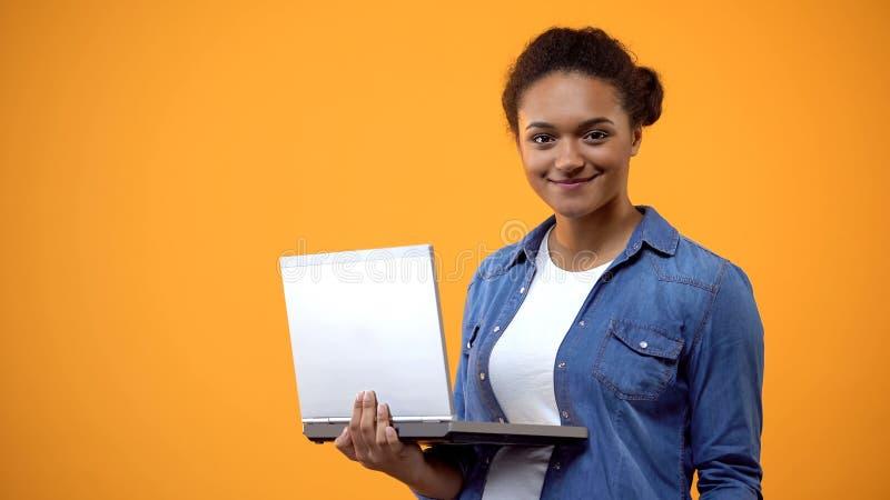 Nätt afrikansk kvinnainnehavbärbar dator, bloggerarbete, online-affärsprojekt royaltyfri foto
