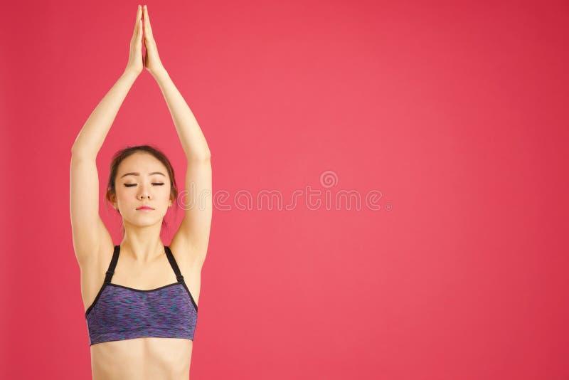 Nätt asiatisk flicka som sträcker stunden som gör aerobics och yoga i a fotografering för bildbyråer