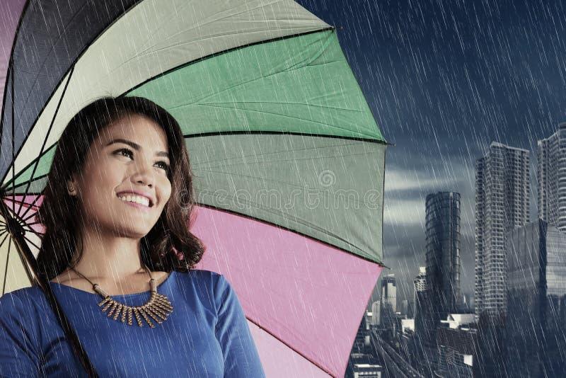Nätt asiatisk kvinna med paraplyet på regn arkivbild
