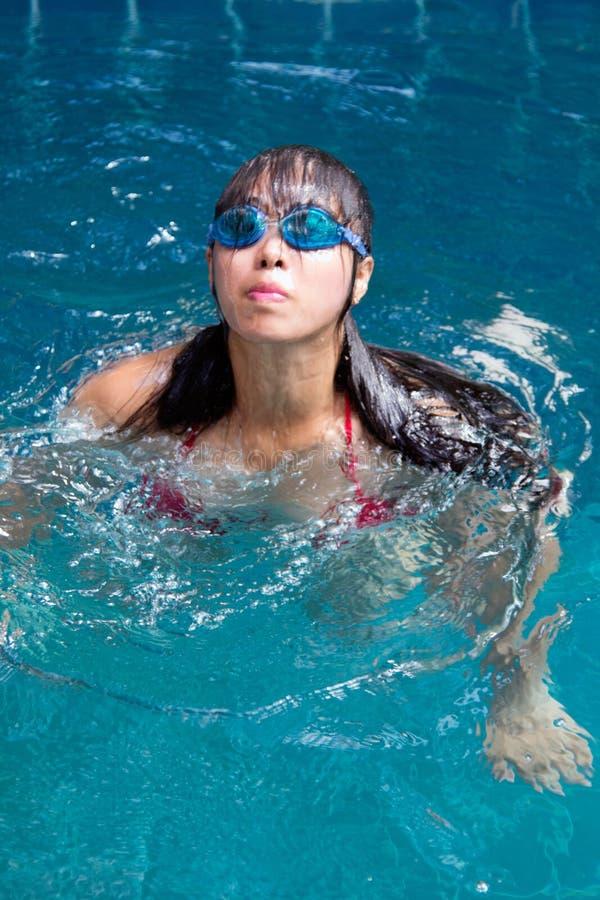N?tt asiatisk kvinna som b?r den r?da bikinin med vattent?ta exponeringsglas som simmar p? simbass?ngen arkivbilder