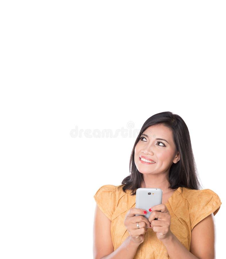 Nätt asiatisk kvinna, text på hennes mobiltelefon med den lyckliga framsidan arkivbild