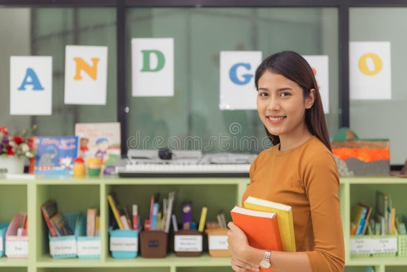 Nätt asiatisk lärare som ler på kameran på baksida av klassrumet på grundskolan royaltyfria foton