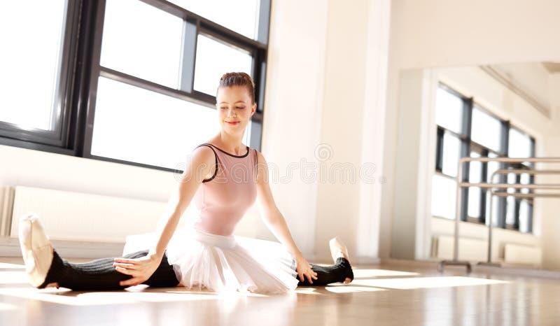 Nätt ballerina som delar henne ben på golvet royaltyfria bilder
