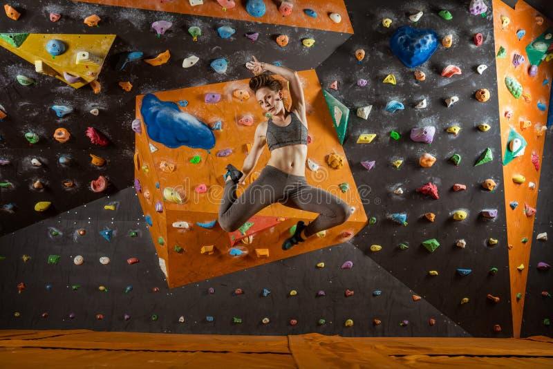 Nätt banhoppning för ung kvinna i klättringidrottshall royaltyfri fotografi