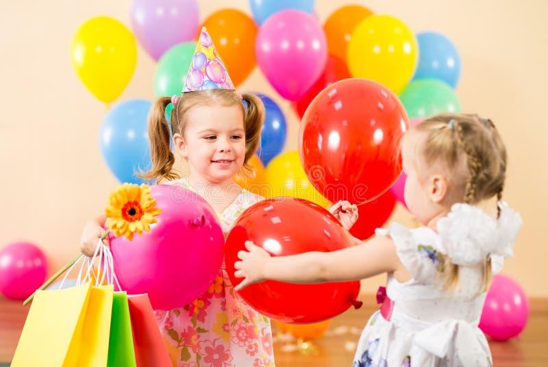 Nätt barn med ballonger på födelsedagdeltagare royaltyfri fotografi