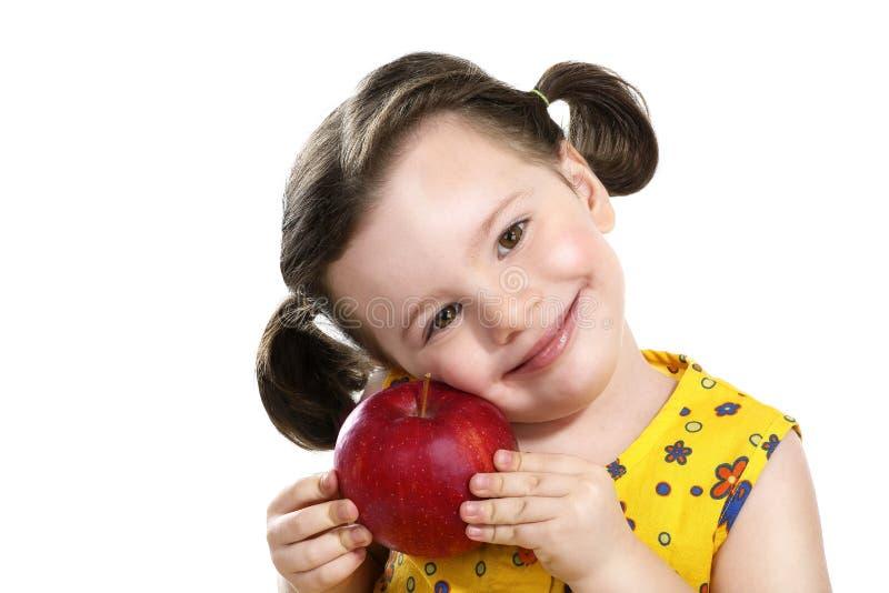 Nätt barn som rymmer ett rött äpple i henne händer royaltyfri foto