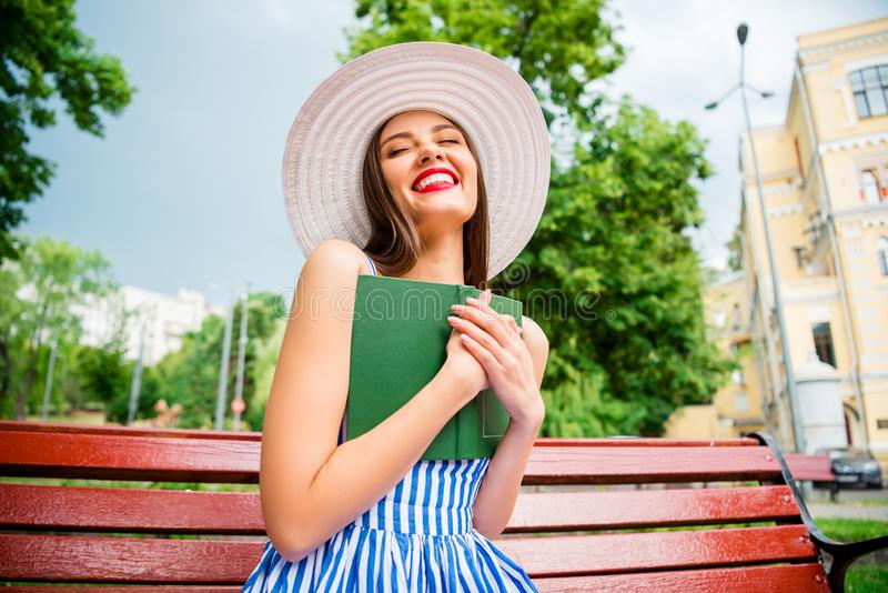 Nätt berättelse för damläsningromans som är extatisk av den sista sittande hemtrevliga hatten och klänningen för frunchklädersol royaltyfri fotografi