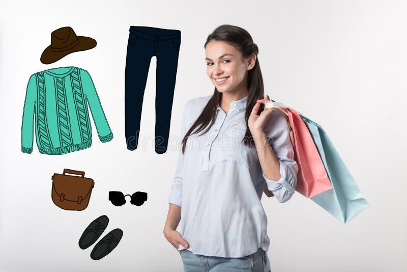 Nätt blogger som ler, medan välja ny kläder arkivfoto