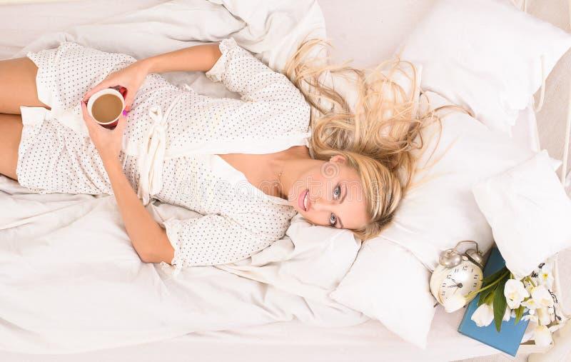 Nätt blond dam med koppen kaffe i säng royaltyfria foton