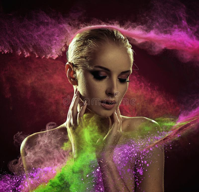 Nätt blond dam som täckas med färgrikt pulver royaltyfria foton
