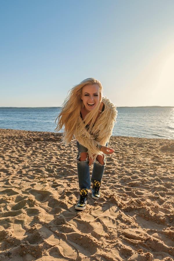 Nätt blond flicka i en ungdomlivsstildräkt på stranden som högt skrattar och ler arkivbild