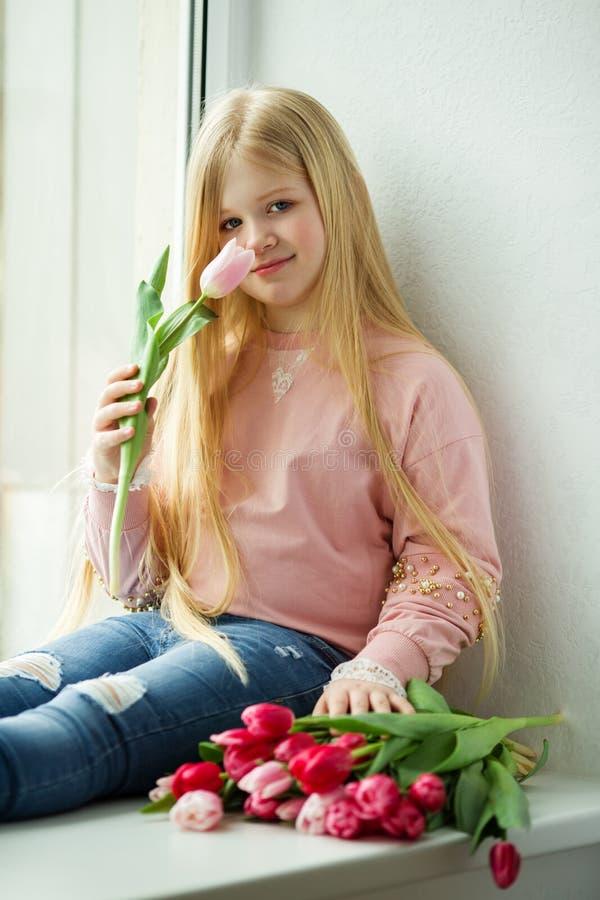 Nätt blond flicka med buketten av rosa blommor för tulpan målat gräs för 2 placerade allt för easter för hinkfågelungebegreppet b arkivbild