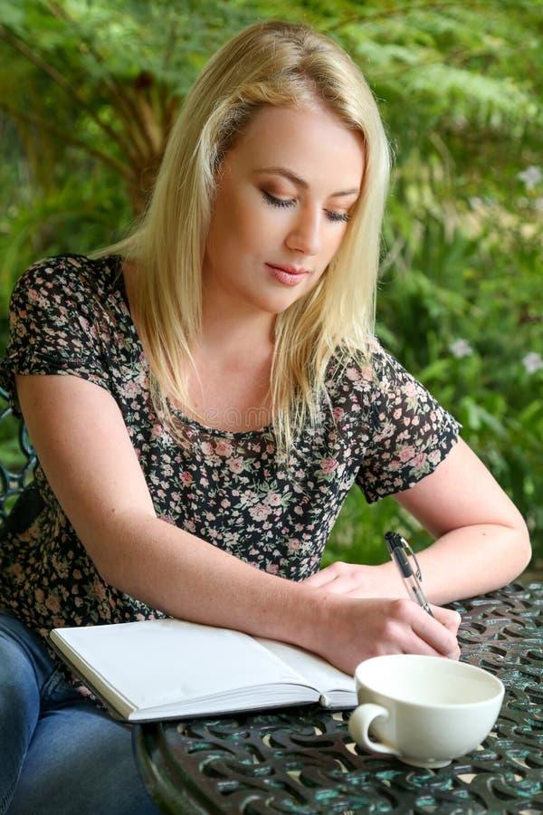 Nätt blond flicka med dagboken arkivfoton