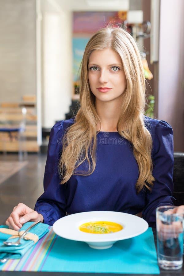 Nätt blond flicka som äter pumpasoppa i restaurang royaltyfri foto