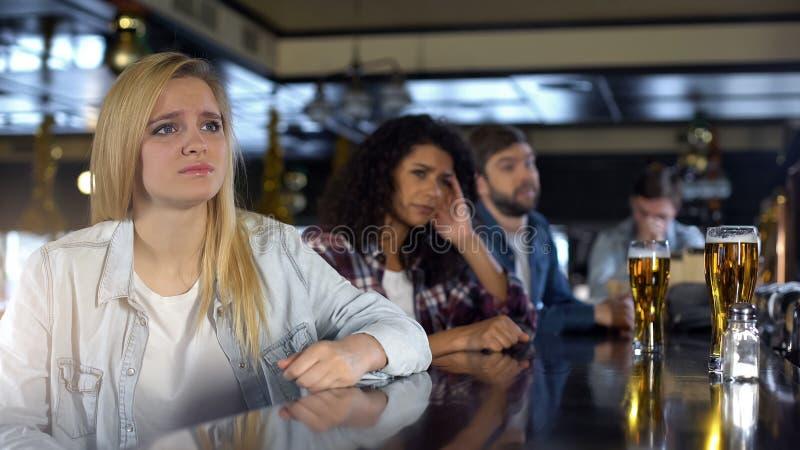 Nätt blond flicka som förargas om den förlorande leken, hållande ögonen på sportar med vänner i bar arkivbild