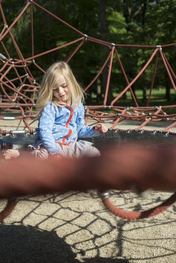 Nätt blond flicka som spelar på rep av den röda rengöringsduken i sommar royaltyfri fotografi