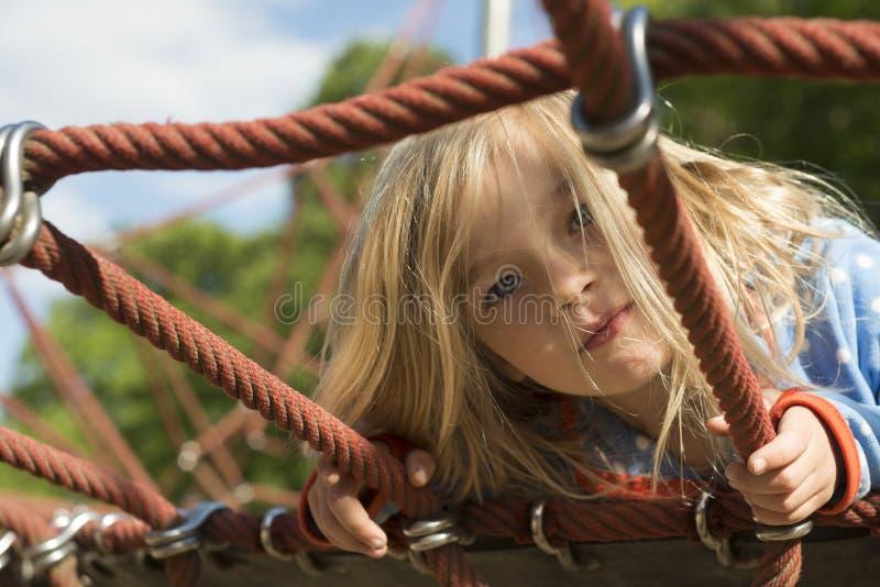 Nätt blond flicka som spelar på rep av den röda rengöringsduken i sommar royaltyfri bild