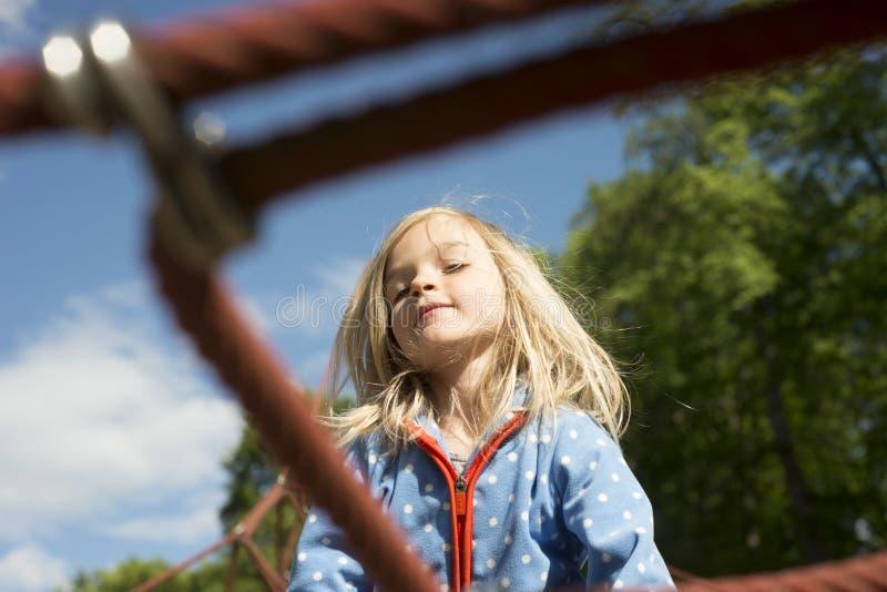 Nätt blond flicka som spelar på rep av den röda rengöringsduken i sommar fotografering för bildbyråer