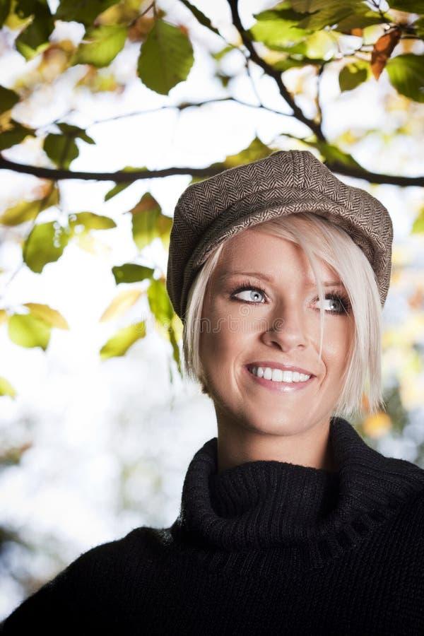 Nätt blond flicka utomhus med bladet i bakgrund fotografering för bildbyråer