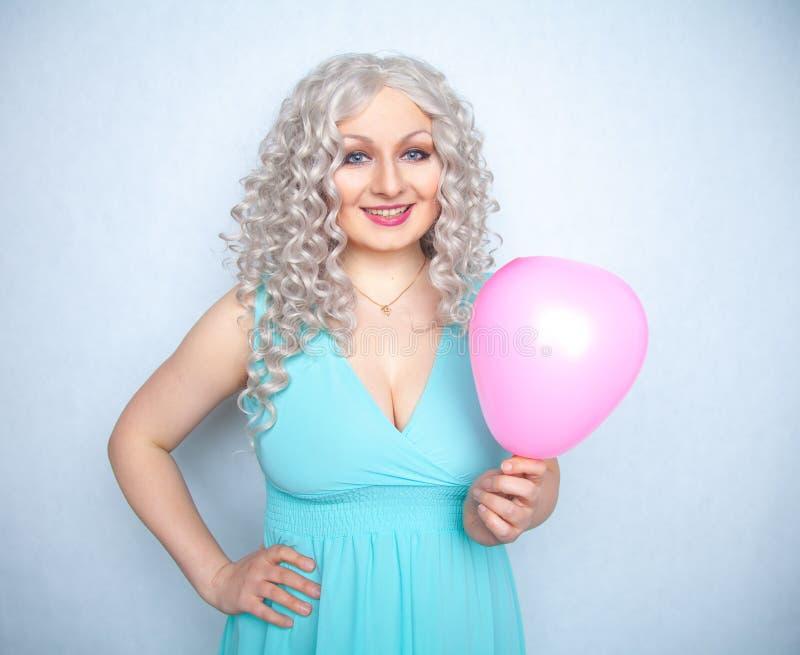 Nätt blond gladlynt flicka med den rosa luftballongen på vit studiobakgrund royaltyfria foton