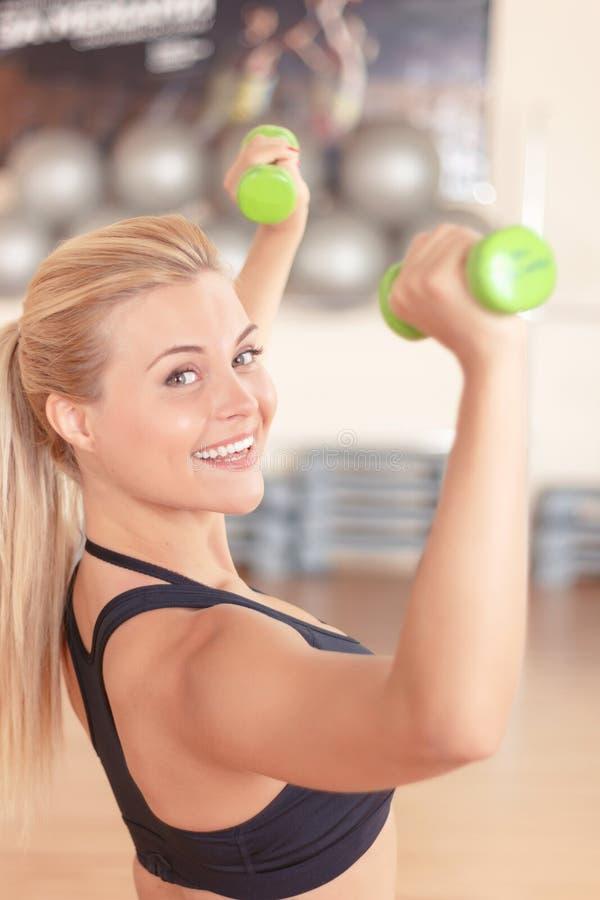 Nätt blond-haired kvinna som gör konditionövningar royaltyfri bild