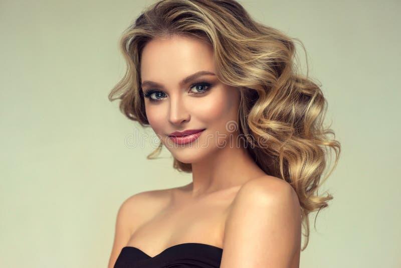 Nätt blond-haired modell med den lockiga lösa frisyren och attraktiv makeup arkivbild