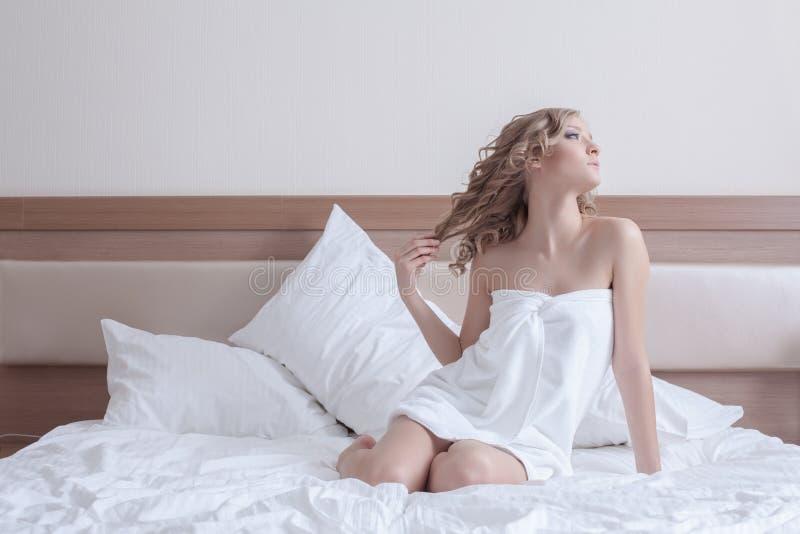 Nätt blond kvinna i handduk på enormt underlag royaltyfri foto