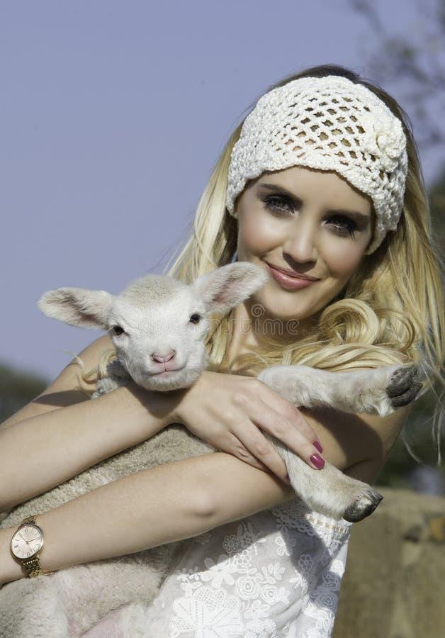 Nätt blond kvinna med den vita virkninghuvudbindeln som rymmer det lilla lammet royaltyfri fotografi