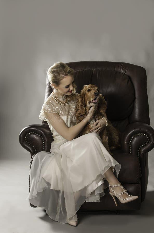 Nätt blond kvinna med hunden på hennes varv arkivbild
