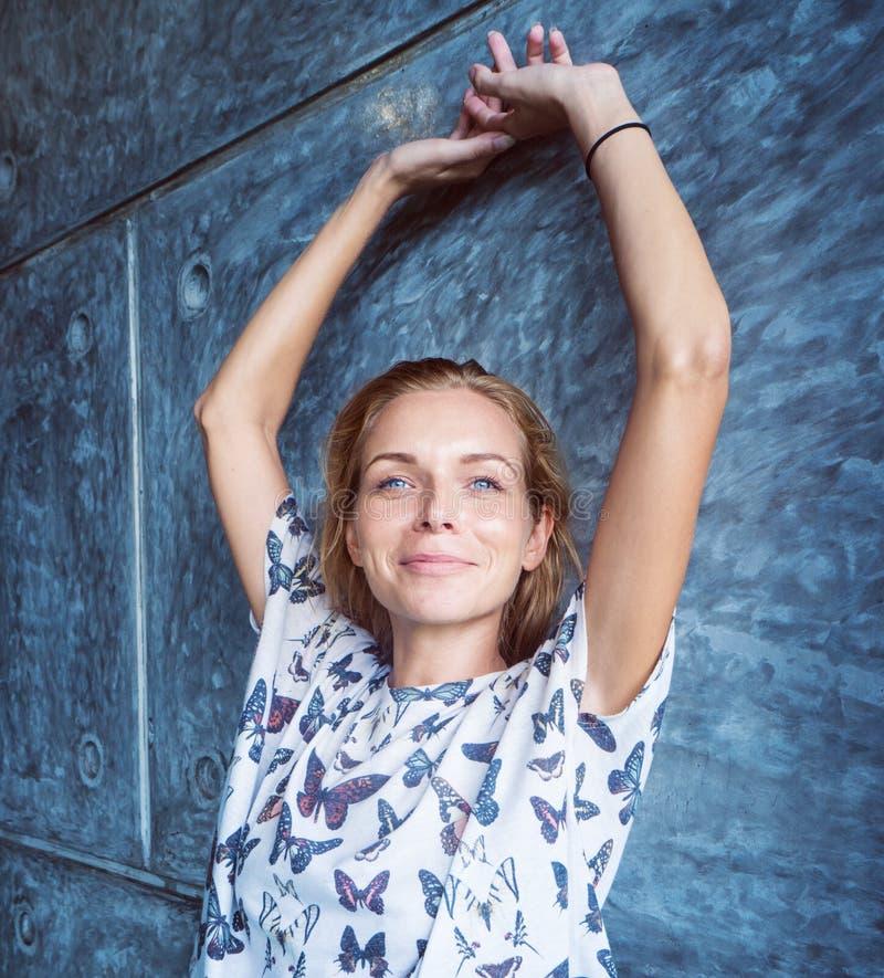 Nätt blond kvinna som ler över den gråa tegelstenväggen fotografering för bildbyråer