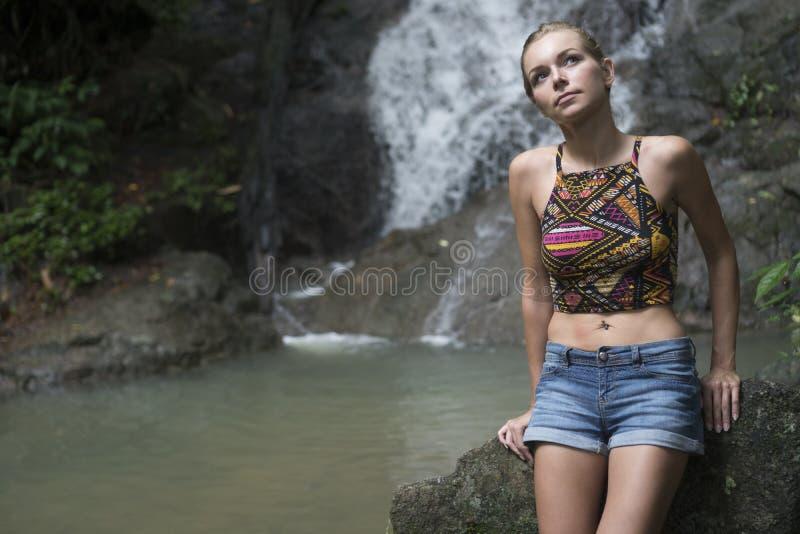 Nätt blond kvinna som sittting på en vagga och ser upp nära vattenfallet royaltyfria foton