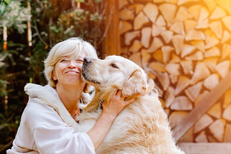 Nätt blond kvinna som spelar med hennes hundgolden retriever arkivbilder