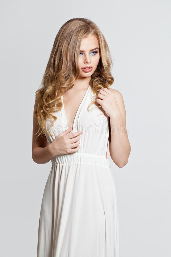 Nätt blond modellstående Elegant kvinna i den vita klänningen på vit bakgrund arkivfoto
