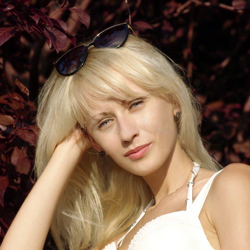 Nätt blondin med solglasögon och mystisk blick. fotografering för bildbyråer