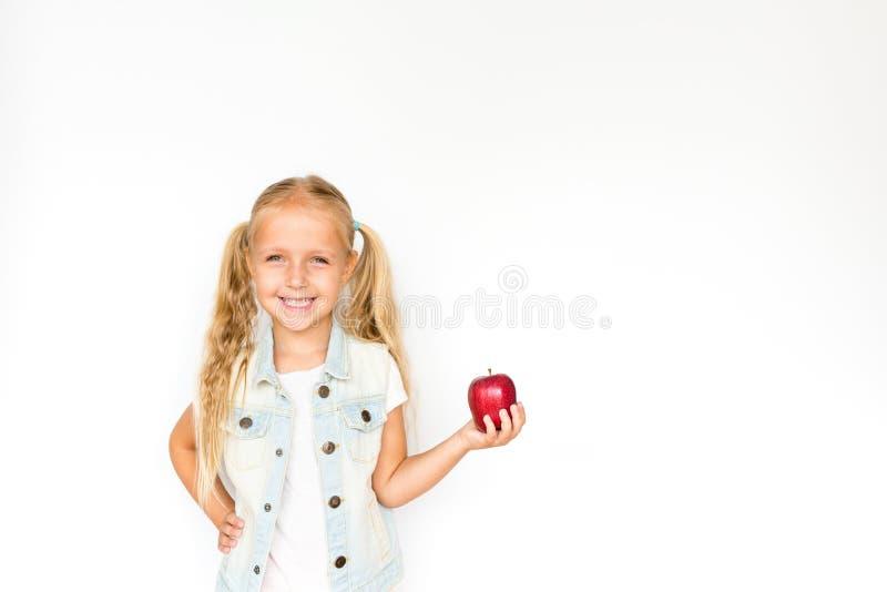 Nätt blont liten flickaanseende på vit bakgrund och rymma det nya röda äpplet sund begreppsmat fotografering för bildbyråer