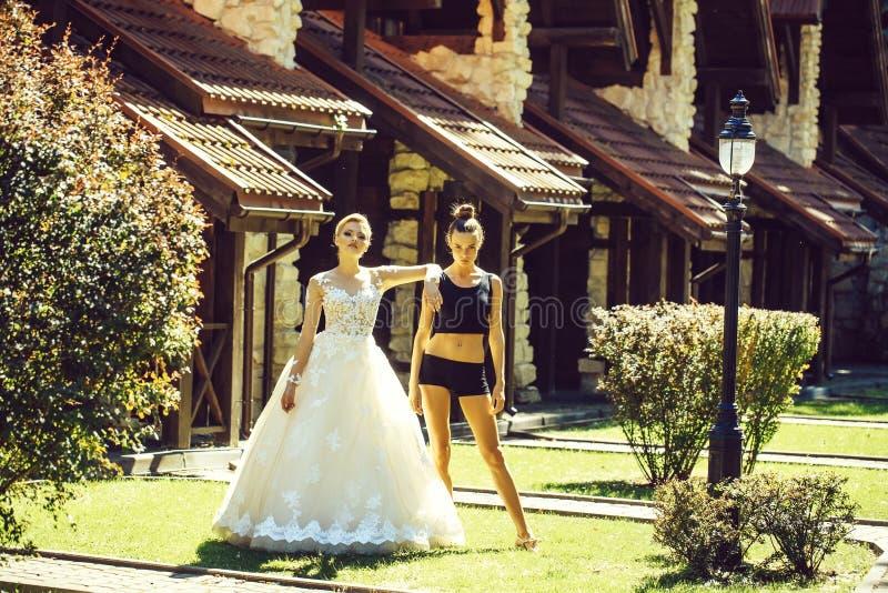 Nätt brud i den vita bröllopsklänningen och färdig flicka arkivbild