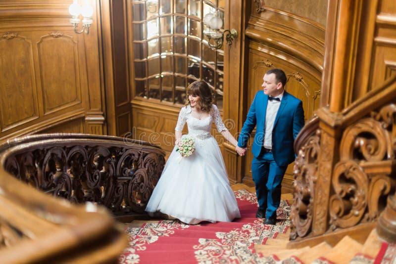 Nätt brud och stilig brudgum som ser in mot att gå upp gammal trätrappa på bakgrunden av den lyxiga inre royaltyfri foto