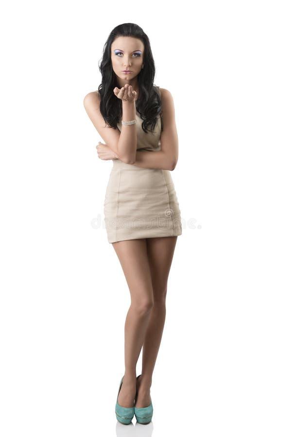 Nätt brunett med den korta klänningen som överför en kyss royaltyfri foto